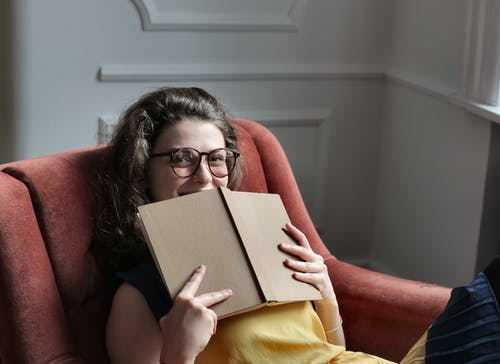 Woman in Brown Framed Eyeglasses Holding a Book