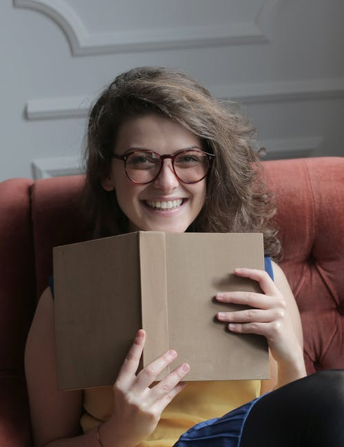 Happy young woman in eyeglasses sitting with book at home