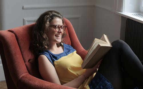 Young woman reading book while sitting on armchair at home