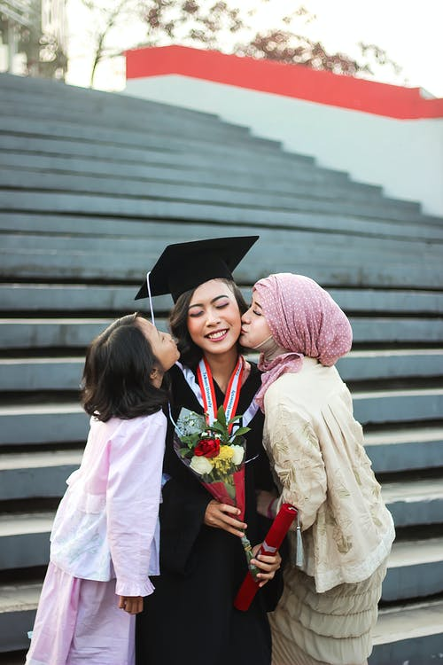 Two Girls Kissing Woman in Graduation Gown