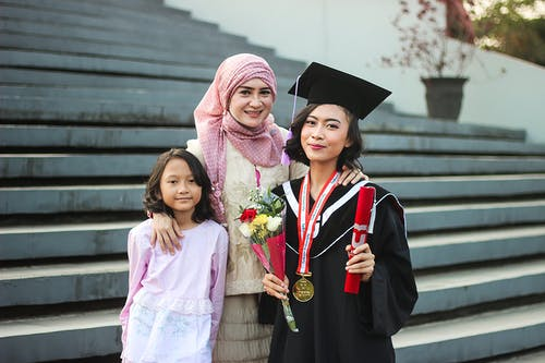 Two Girls Standing Near Woman Wearing Graduation Gown