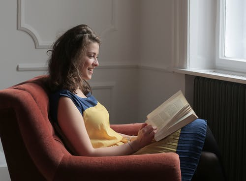 Woman  Reading a Book Sitting on Red Sofa Chair