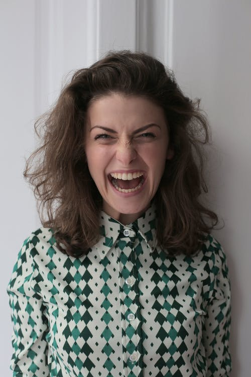 Extremely happy young female in knitted dress standing with open mouth near white wall in apartment and looking at camera