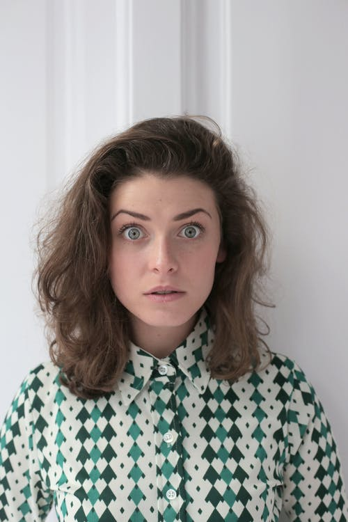 Shocked young lady with short wavy hair in knitted blouse standing near white wall in flat and looking at camera with wide open eyes