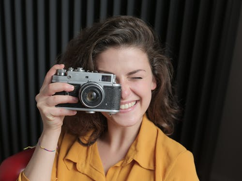 Woman in Yellow Shirt Holding Gray and Black Camera