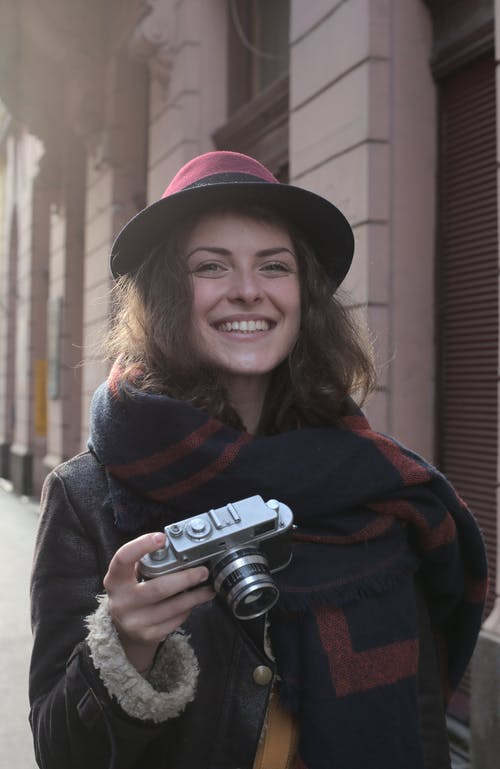 Smiling Woman in Black and Red Jacket Holding Black and Silver Camera