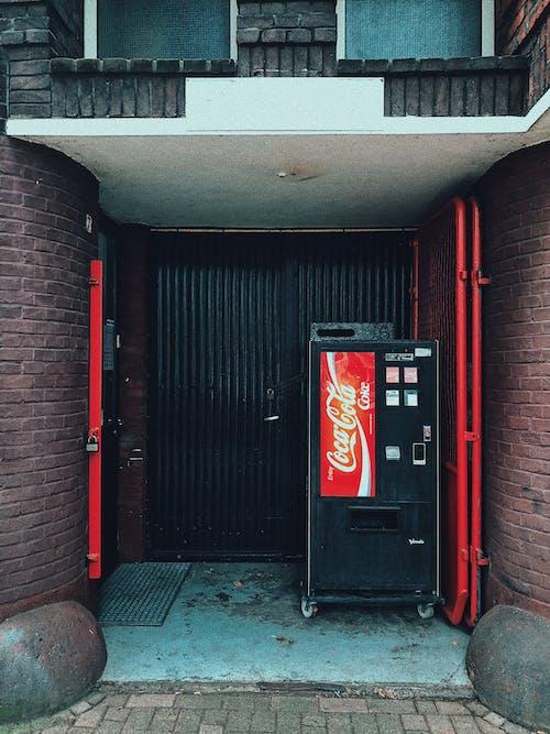Vending Machine Beside Black Wooden Door