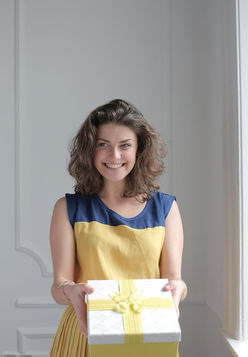 Woman in Blue and Yellow Sleeveless Dress Holding Yellow Box Present