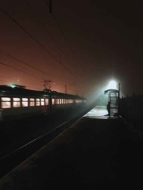 Silhouette of Person Standing on Train Rail during Night Time
