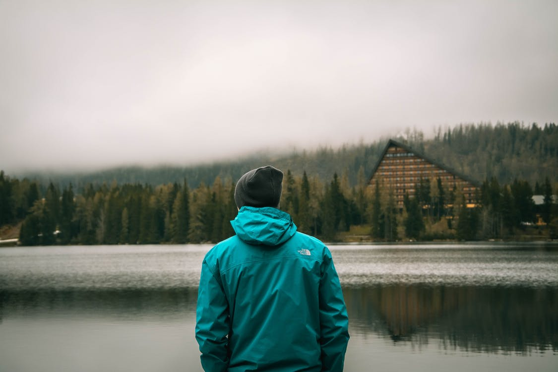 Person in Green Hoodie Standing Near Lake