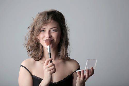 Woman in Black Spaghetti Strap Top Holding a Make up Brush