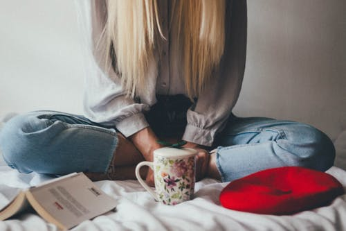 Woman Sitting On A Bed Beside Mug And Books