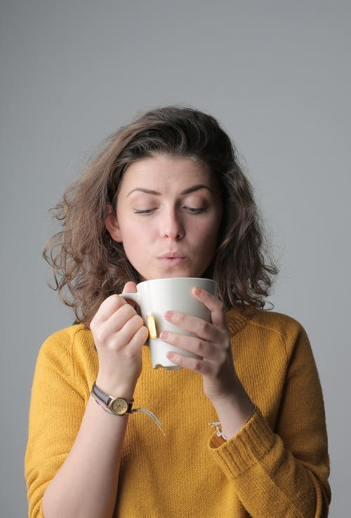 Woman in Yellow Sweater Holding White Ceramic Mug