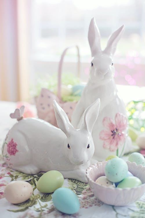 White Rabbit Figurine Beside Easter Eggs on Floral Textile