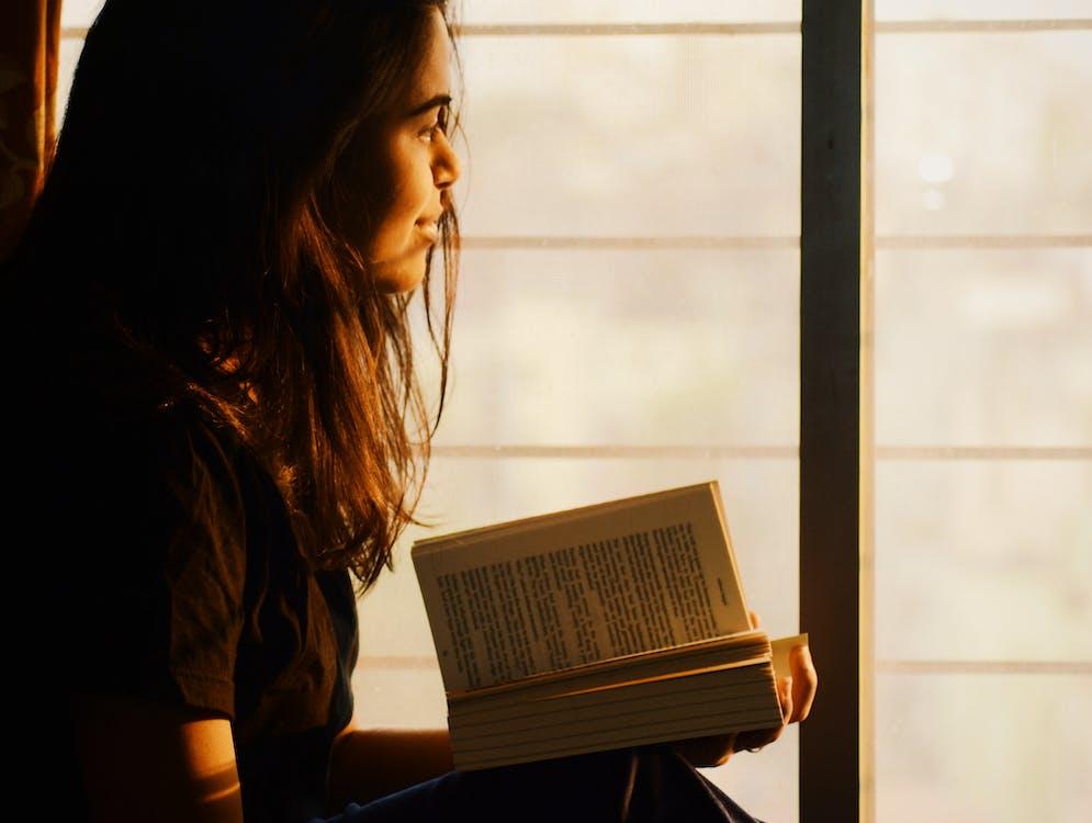 Woman Reading Book on Window