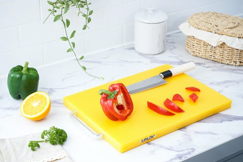 Red Bell Pepper On Yellow Chopping Board
