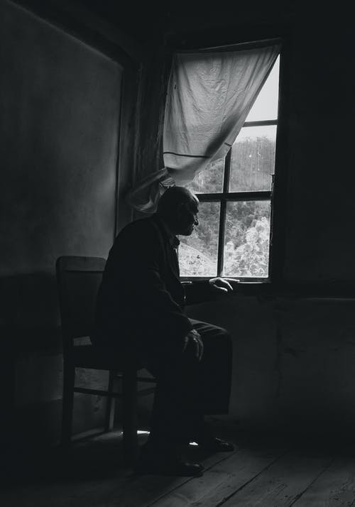 Man Sitting On A Chair Looking Out The Window