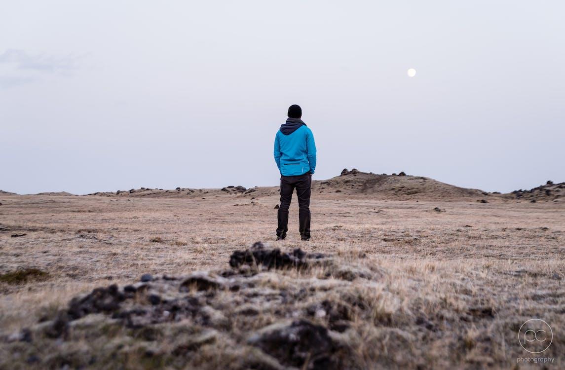 Man in Blue Hoodie Standing on Brown Grass