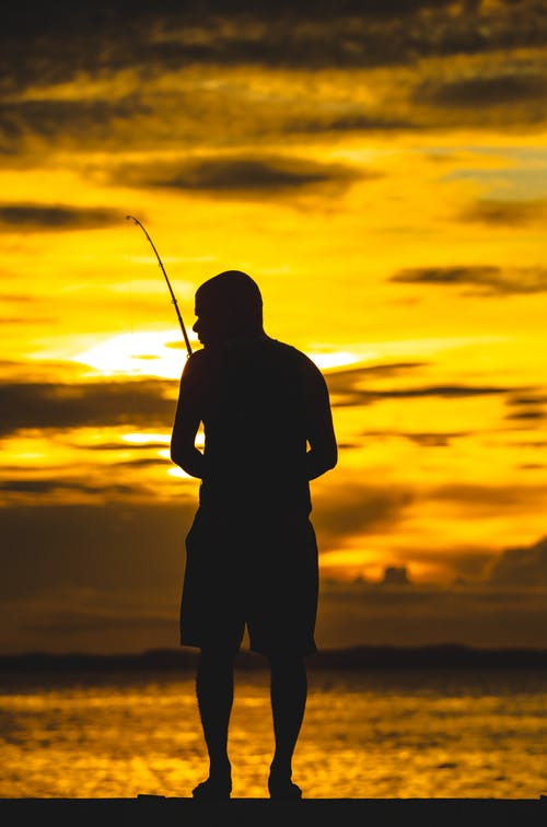 Silhouette of Man Holding Fishing Rod during Sunset