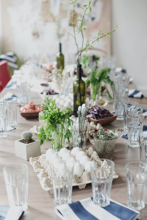 Creative table setting for celebration of Easter with green tree branches in vine bottles