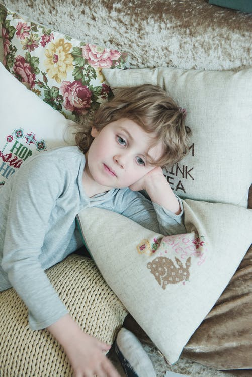Girl in Gray Sweatshirt Leaning on White Pillow