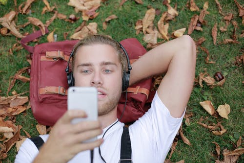 Man in White Shirt Lying on Red Backpack Holding White Smartphone