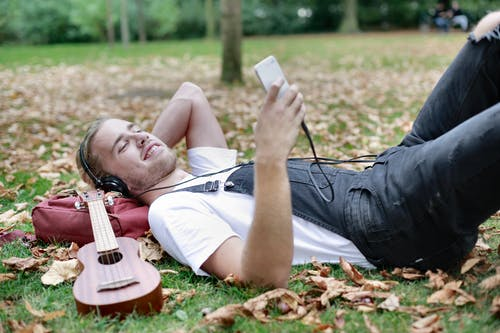 Man in White Shirt Lying on Green Grass Field Holding White Smartphone