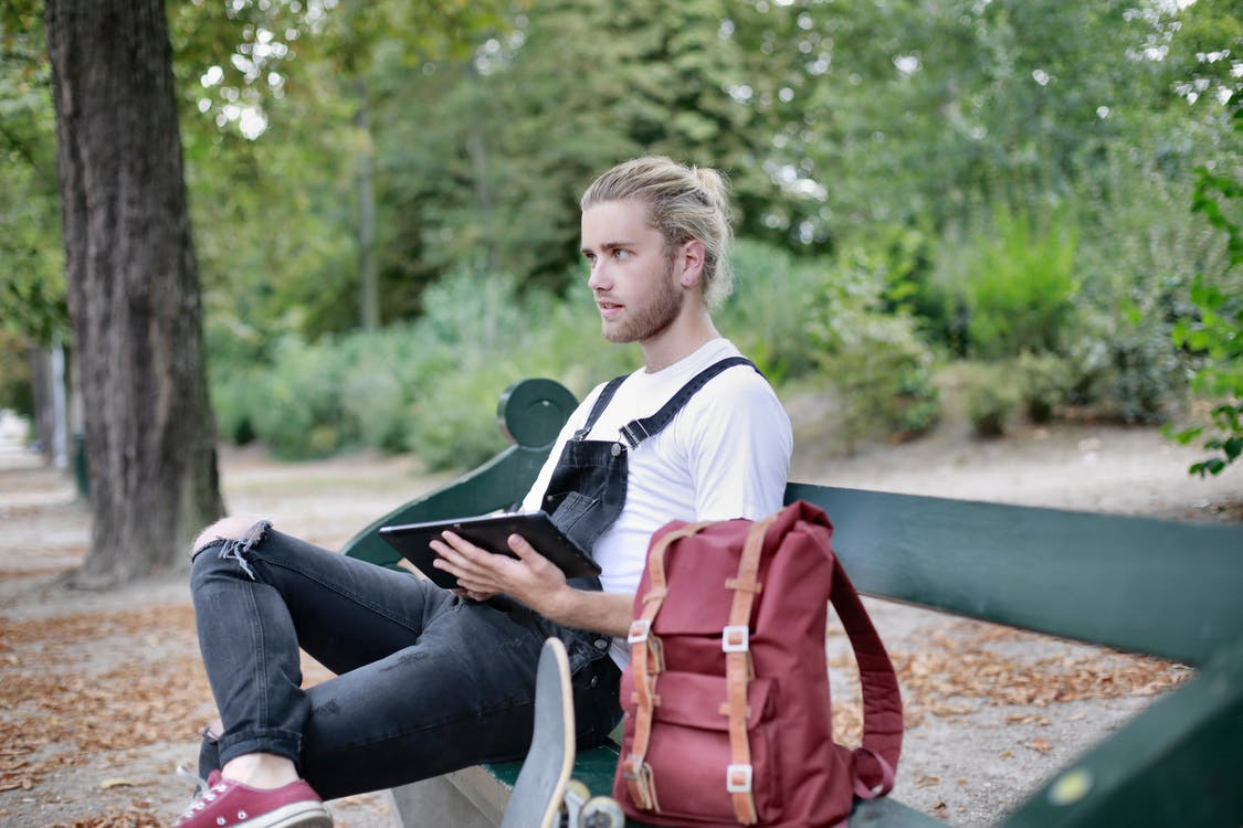 Man in White Shirt and Black Pants Sitting on Bench Holding an Ipad