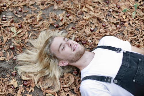 Man in White Shirt Lying on Brown Dried Leaves