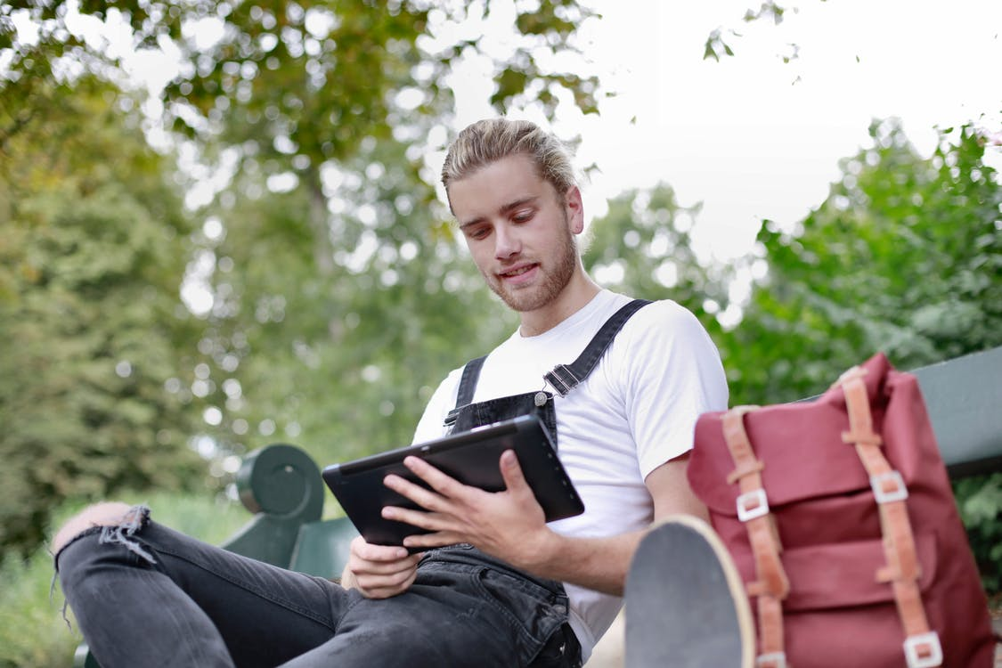 Man in White Crew Neck T-shirt and Black Pants Holding His Ipad