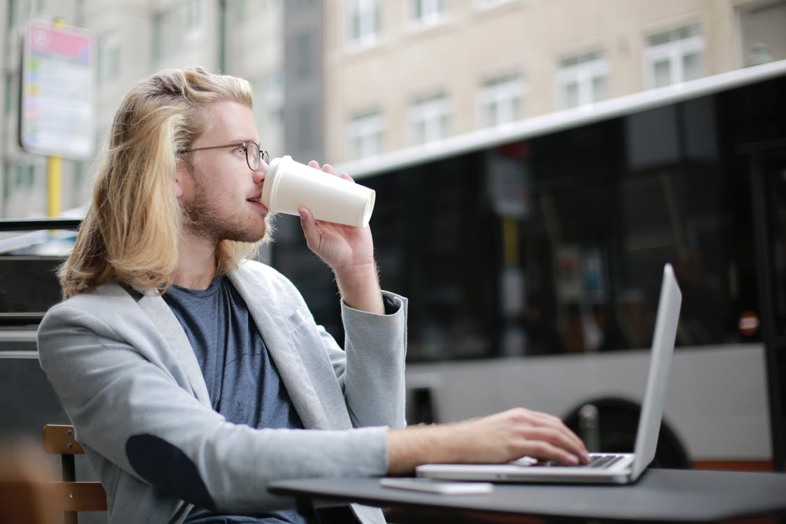 Man Drinking Coffee while Working on His Laptop