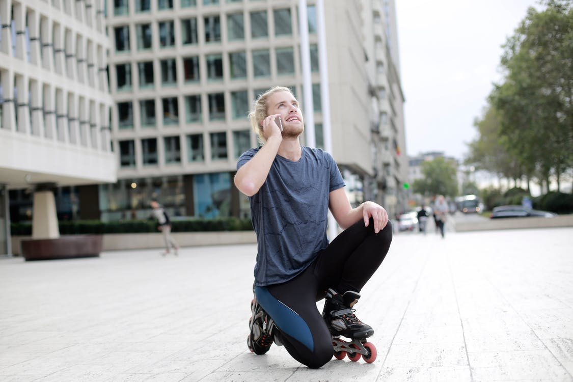 Man in Blue Crew Neck T-shirt and Black Pants Kneeling on Gray Concrete Floor during