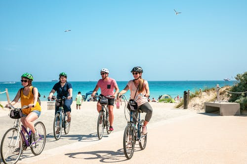 People Riding Bicycles At The Beach