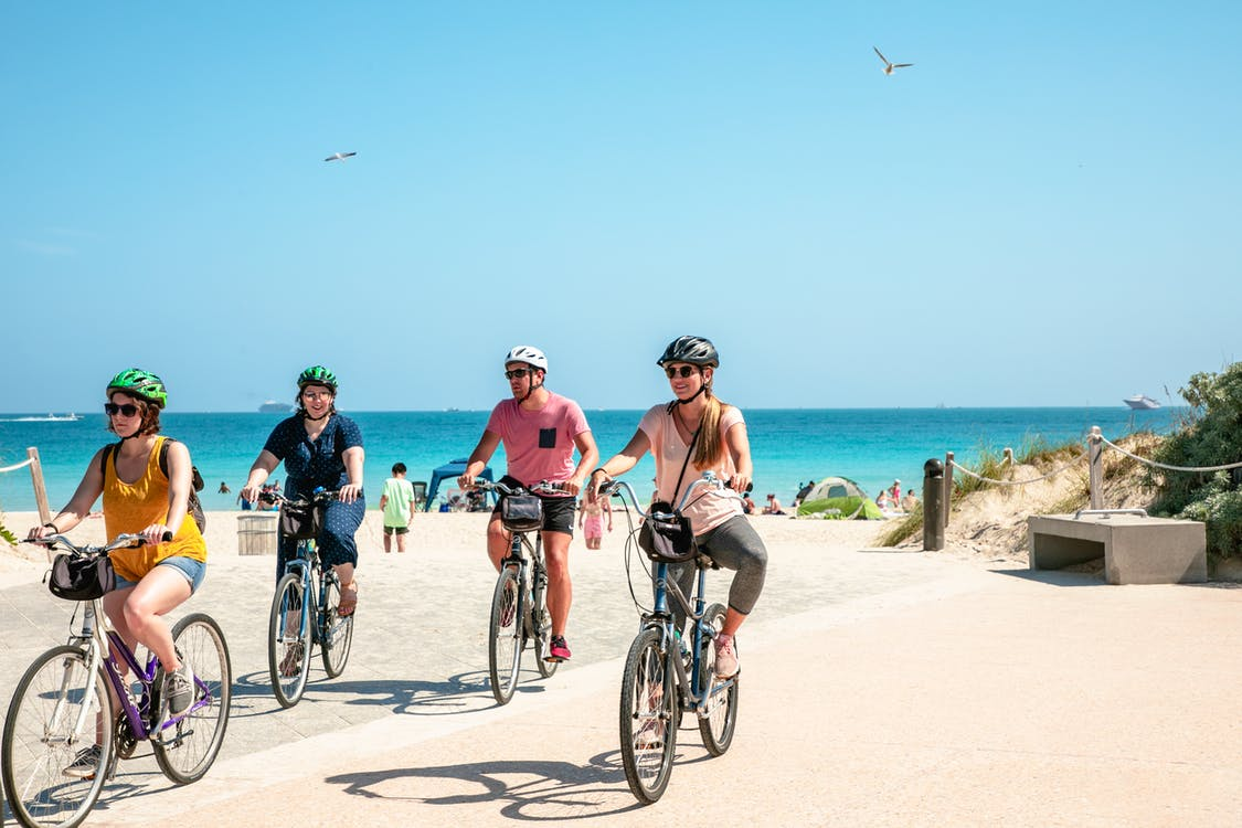 People With Helmets Riding Bicycles At The Beach