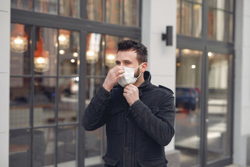 Man in Black Coat Drinking from White Ceramic Mug