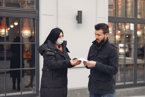 Young woman giving medical mask to man against building