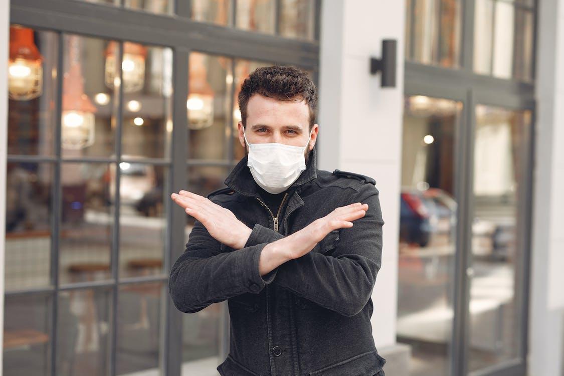 Man in Black Long Sleeve Shirt Wearing White Face Mask