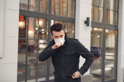 Unhealthy male wearing warm jacket and protective facial mask coughing while standing alone on urban street against city restaurant exterior in cold season