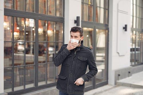 Worried young man in medical mask on urban street during coronavirus pandemic