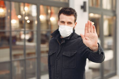 Concerned young man in medical mask on urban street during coronavirus pandemic