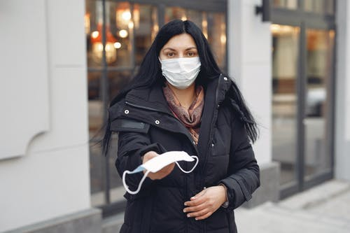 Young woman wearing medical mask and black down jacket on urban street in cold season
