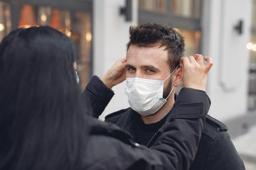 Young couple adjusting medical mask against blurred urban building
