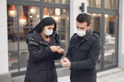 Young couple in medical masks disinfecting hands against urban building facade