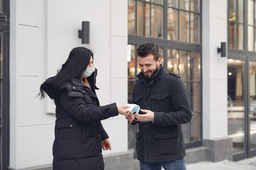 Cheerful bearded man taking protective facial mask from girlfriend while standing together against city building facade during coronavirus pandemic at daytime