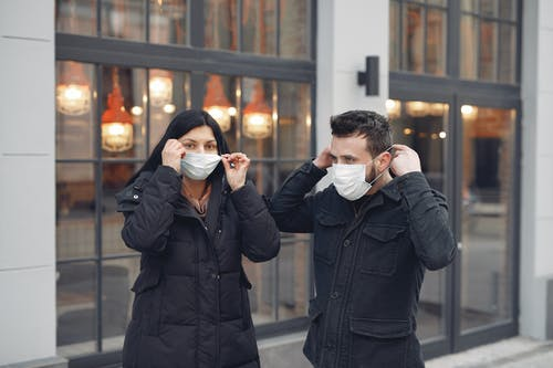 Young couple adjusting medical masks against urban building exterior