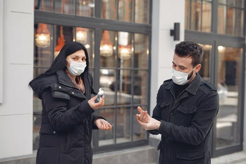 Careful man and woman in warm outerwear wearing protective facial masks applying antiseptic on hands while standing on city street during coronavirus pandemic