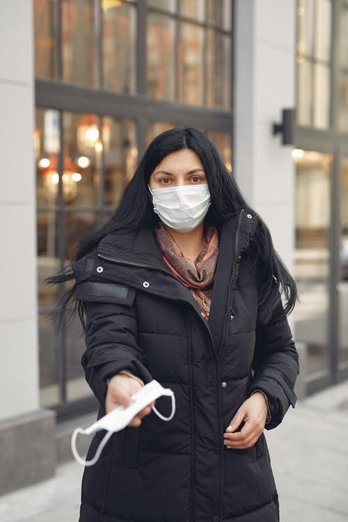 Woman in Black Leather Jacket Wearing White Mask