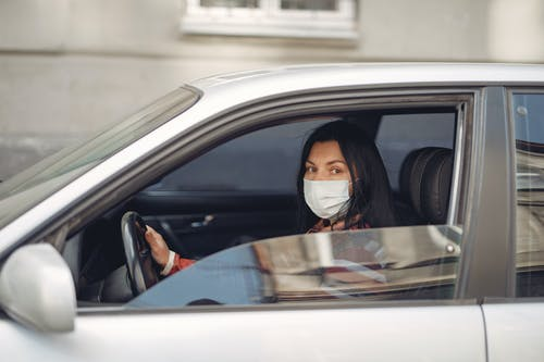 Young woman wearing medical mask driving car