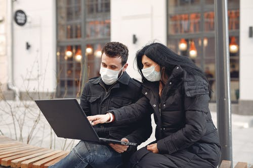 Concentrated young couple in medical masks using laptop on city street together
