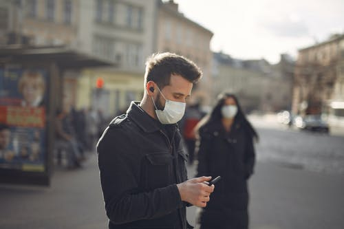 Focused man in medical mask using smartphone on urban street in cold season